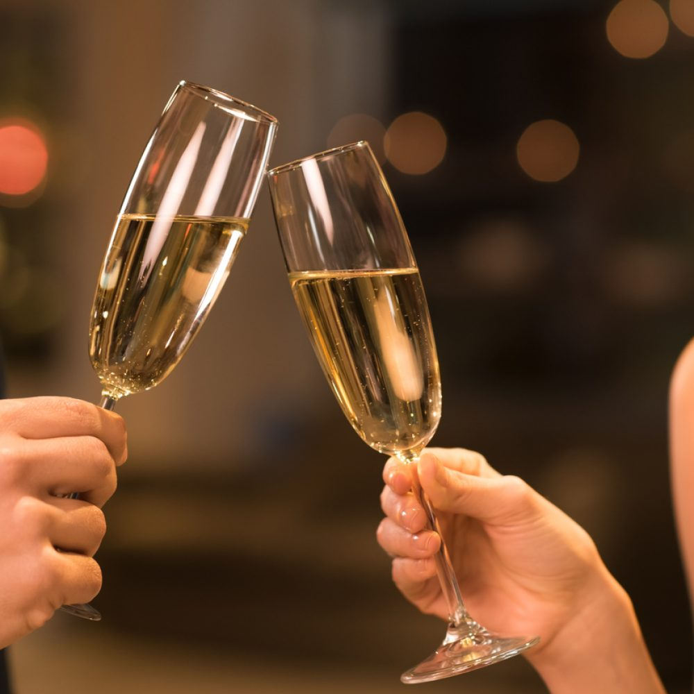 Couple toasting champagne glasses in a luxury restaurant. Couple enjoying meal and drinks in a restaurant. Young loving couple celebrating their anniversary, new year.