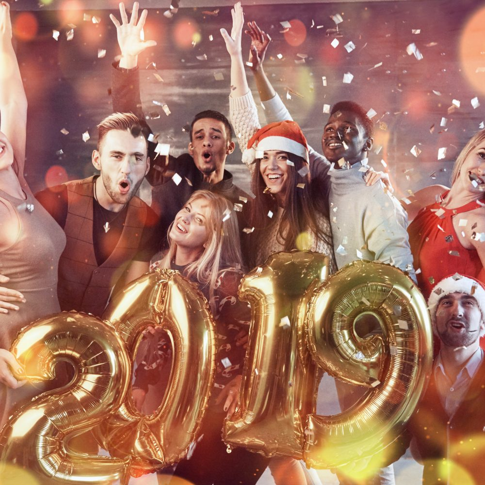 New 2019 Year is coming! Group of cheerful young multiethnic people in Santa hats carrying gold colored numbers and throwing confetti on the party. Bokeh light soft effect.
